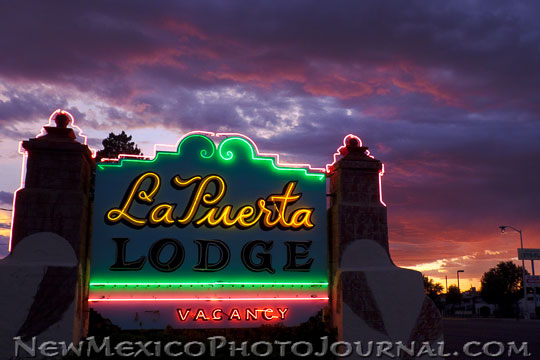 La Puerta's neon sign against a sunset background.