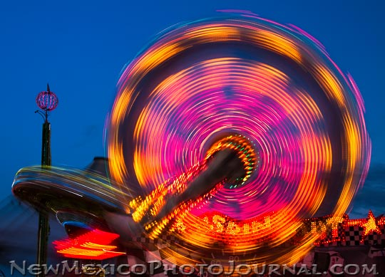a ride spins with colorful colors on the midway at the new mexico state fair
