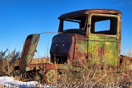 an old rusty truck, the grill held upright with a stick