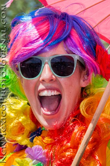 A woman with vividly rainbow-colored hair revels at the Albuquerque Pride Parade