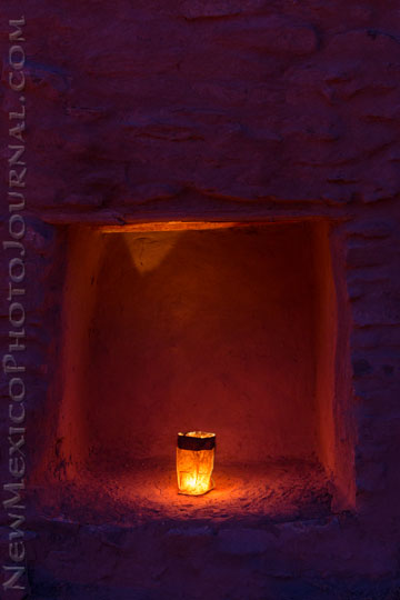 A luminaria burns in a nicho at Jemez State Monument