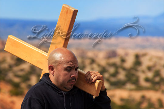a man carrying a cross participates in the Good Friday pilgrimage to Chimayo