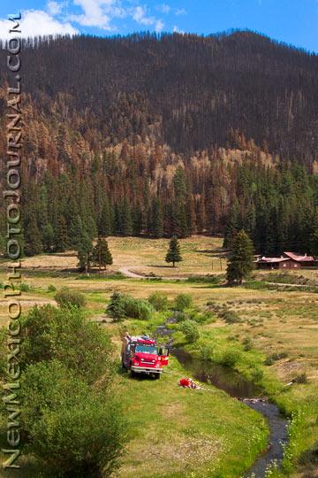 a fire truck in a meadow alongside the East Fork of the Jemez River