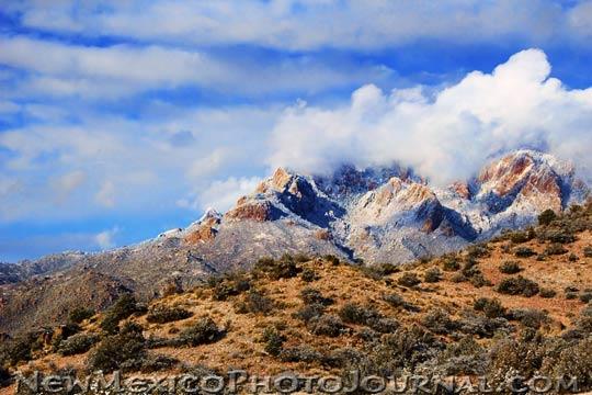 Snow swirls around the Sandia mountains