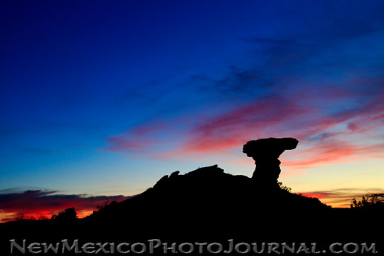 Camel Rock, in Tesuque, is silhouetted against a colorful sunset.