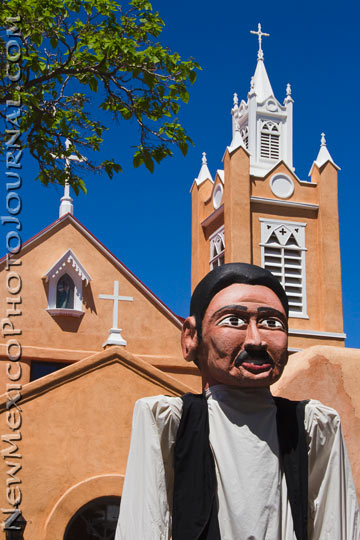 a larger than life size puppet in front of the san felipe de neri church in old town albuquerque
