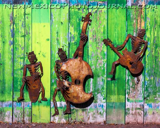 A band of rusted musicians resides on a old green fence in Albuquerque's South Valley.