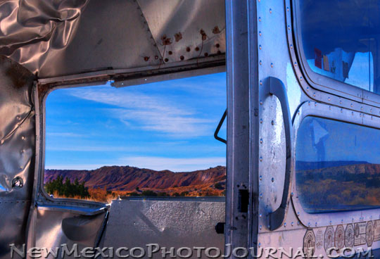 New Mexican landscape through the windshield of an old Airstream trailer
