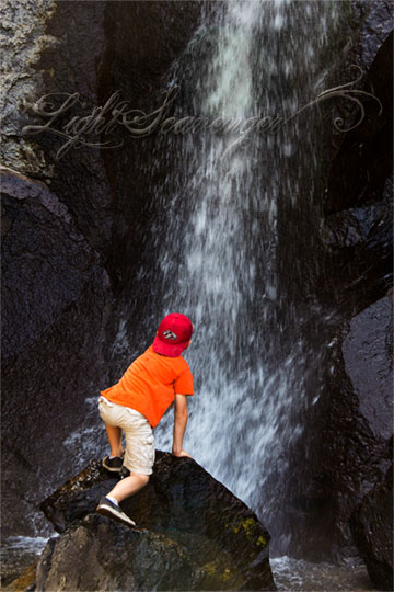 A small boy climbs a rock at the base of a waterfall.
