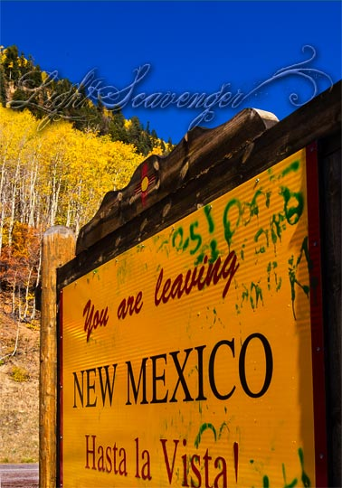 A yellow and red sign on the state line between New Mexico and Colorado, with a background of yellow aspens.